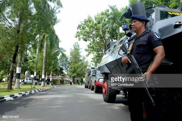 CORRECTION An Indonesian policeman stands guard by the armoured vehicles at a security post in North Sumatra's police headquarters in Medan city on...