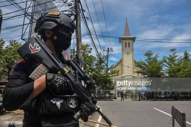 An Indonesian policeman stands guard outside a church after an explosion in Makassar on March 28, 2021.