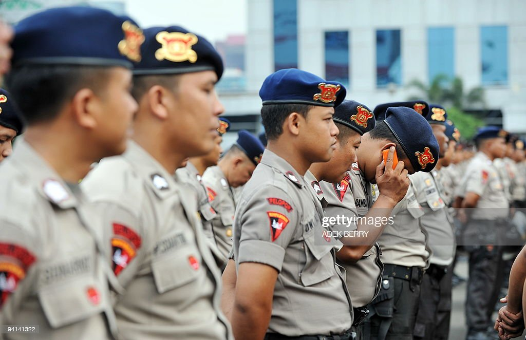 An Indonesian Policeman Talks On A Telephone Whilst Participating In Roll Call Jakarta