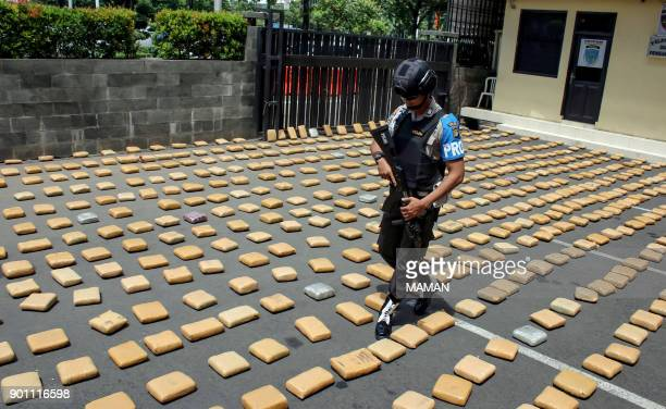 An Indonesian policeman walks amongst bricks of tightlywrapped cannabis during a press conference in Jakarta on January 4 2018 Indonesian authorities...