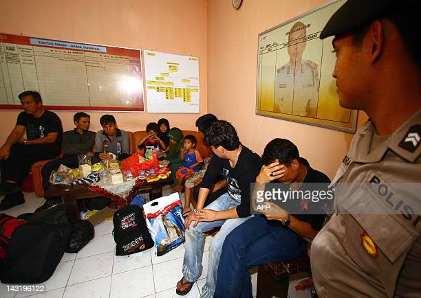 An Indonesian policeman watches over a group of Afghan asylum seeker at a police station in Malang town East Java province early April 21 2012...