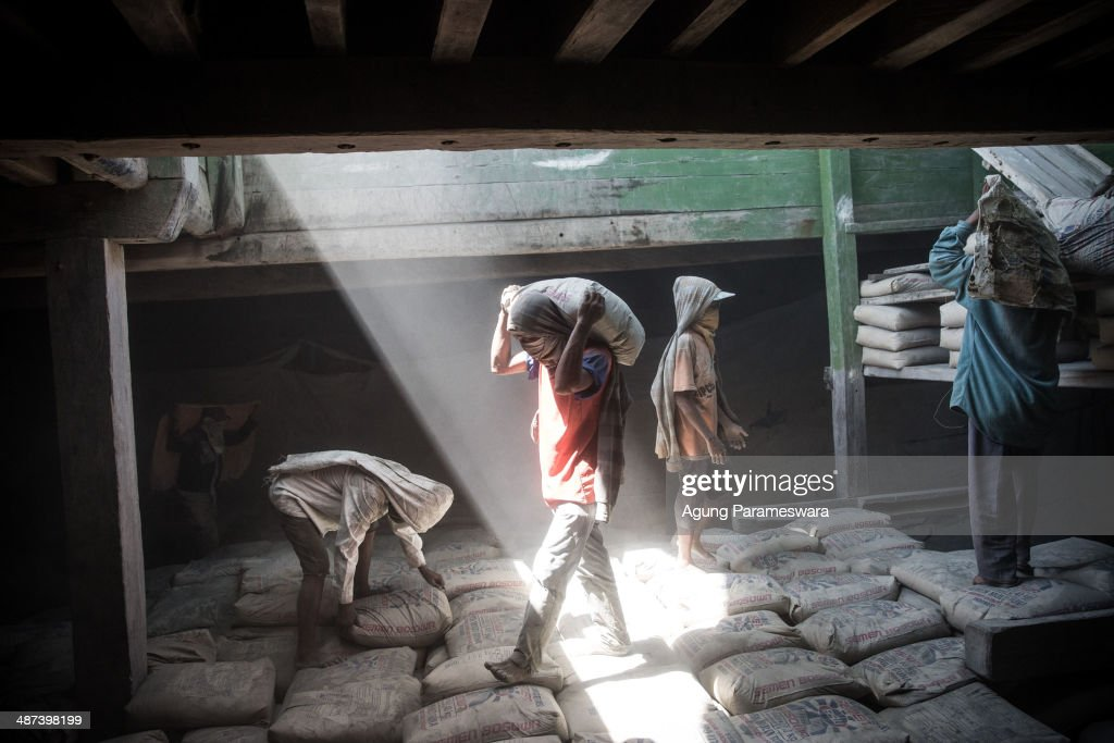 An Indonesian porter carries a sack of cement to load on a traditional wooden ship at Paotere Harbor on April 30, 2014 in Makassar, Indonesia. Tomorrow, around the world will observe International Labour Day, a day to commemorate the period of civil unrest in the late 19th century when workers in industrialised countries agitated for better working conditions, higher wages, and caps on their working day and week. Men labours in Paotere harbour earn their living as a porter to carry sack of cement, rice, flour and bean on their back. They are obliged to live as a small labor and bound to it routine, forced to works all day only for gain a few money. They only get paid between Rp.15.000 (USD 1.33) and Rp.30.000 (USD 2.67) per day. Paotere is the harbour in the north of Makassar where traditional Buginese sailing boats (phinisi) load and unload their cargo.