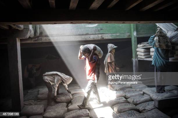 An Indonesian porter carries a sack of cement to load on a traditional wooden ship at Paotere Harbor on April 30 2014 in Makassar Indonesia Tomorrow...