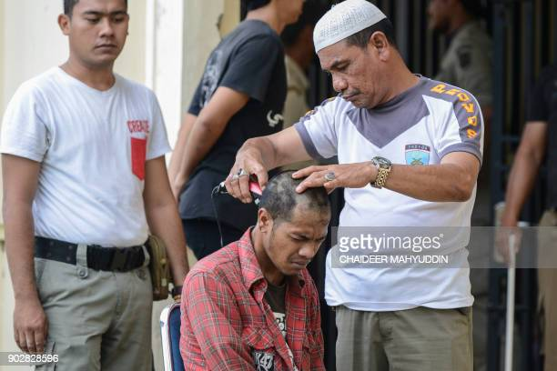 An Indonesian 'punk' has his head shaved after he and a group of 30 others were detained by Sharia police in Banda Aceh on January 9 2018 Some claim...