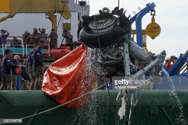 An Indonesian rescue team lift a pair tires from the illfated Lion Air flight JT 610 off Karawang in the Java Sea on November 4 2018 An Indonesian...