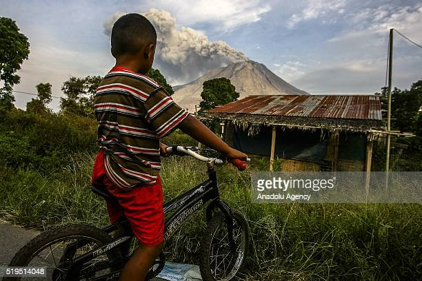 An Indonesian resident witnesses the Sinabung Mountain spews volcanic ash in Karo as seen from Kuta Tengah village in Karo district in North Sumatra...