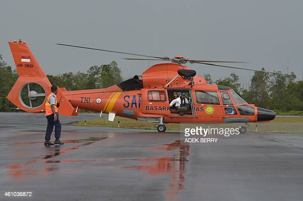 An Indonesian search and rescue helicopter lands carrying bodies of passengers on AirAsia flight 8501 in Pangkalan Bun on January 5 2015 Weather was...