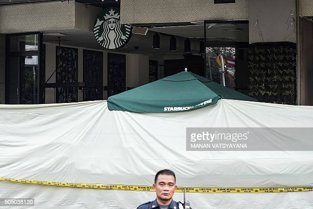 An Indonesian security guard stands guard in front of the damaged Starbucks building in Jakarta on January 15 a day after a series of explosions hit...