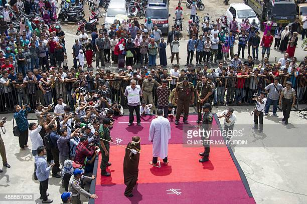 An Indonesian Sharia police whips a man during a public caning ceremony outside a mosque in Banda Aceh, capital of Aceh province on September 18,...