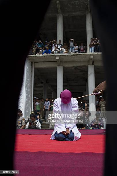An Indonesian Sharia police whips a woman arrested for sexual offense during a public caning ceremony outside a mosque in Banda Aceh capital of Aceh...