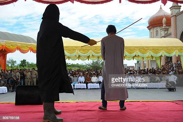 An Indonesian Sharia policeman whips a man and 35 others during a public caning punishment at a Mosque in Meulaboh on the west coast of Aceh province...