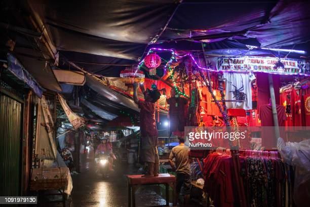 An Indonesian shopkeeper installing lanterns at a shop selling Chinese New Year decorations at night in the Chinatown in Jakarta Indonesia on January...