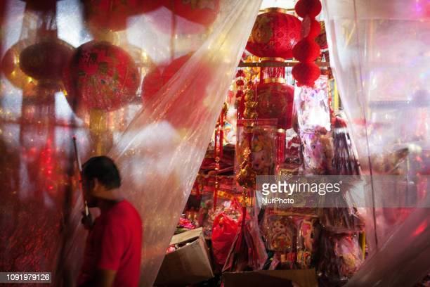 An Indonesian shopkeeper open the plastic curtain after the rain at a shop selling Chinese New Year decorations at night in the Chinatown in Jakarta...