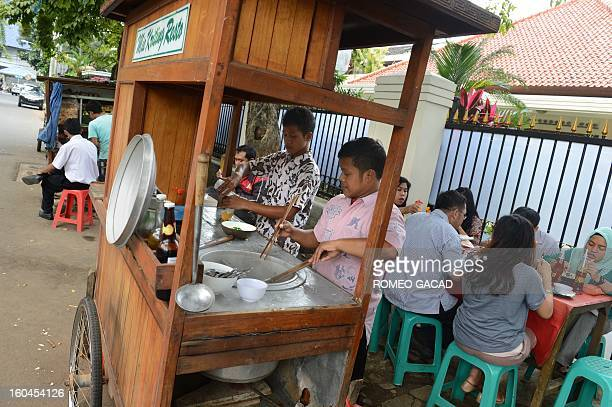 An Indonesian street food vendor prepare meals in an office and residential area in Jakarta market on February 1 2013 Indonesian inflation hit a...