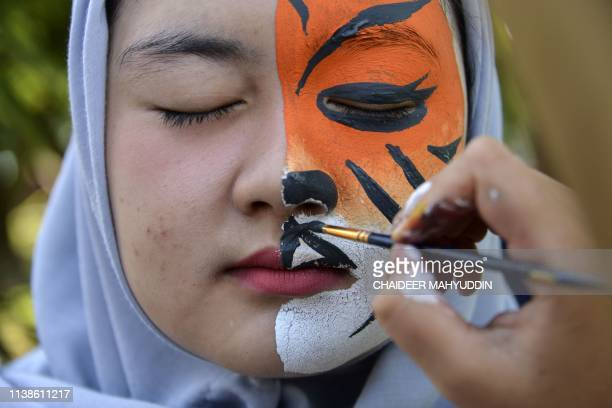 An Indonesian student gets her face painted during an Earth Day rally in Banda Aceh on April 22 2019