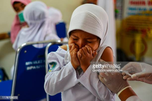 An Indonesian student reacts while being vaccinated for diphtheria at a school in Banda Aceh on October 29, 2019.