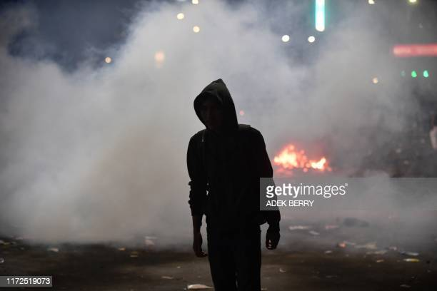 An Indonesian student stands amidst tear gas fired by police during a protest outside the parliament building in Jakarta on September 30, 2019. -...
