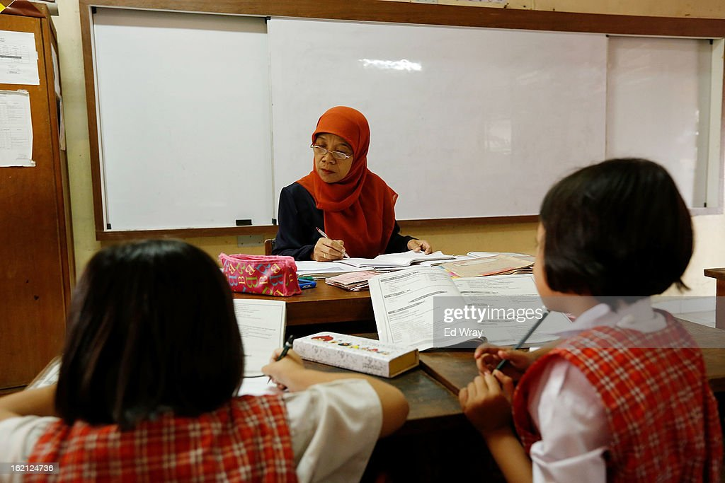 An Indonesian teacher checks her notebook as students study during a 3rd grade social studies class on February 19, 2013 in Jakarta, Indonesia. A new schools curriculum to take effect in July, 2013 has drawn criticism for its plans to drop science and english classes to provide more time for social and religious education, at a time when Indonesian students are falling behind other countries in the region in Science and Math.