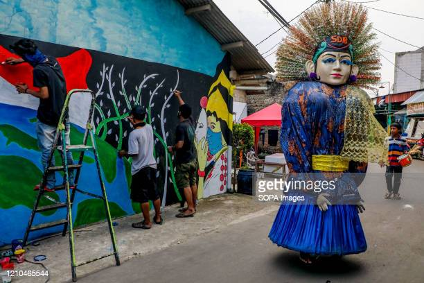 An Indonesian traditional giant puppet called 'Ondel-ondel' walks past local artists drawing a coronavirus awareness graffiti during a lockdown....