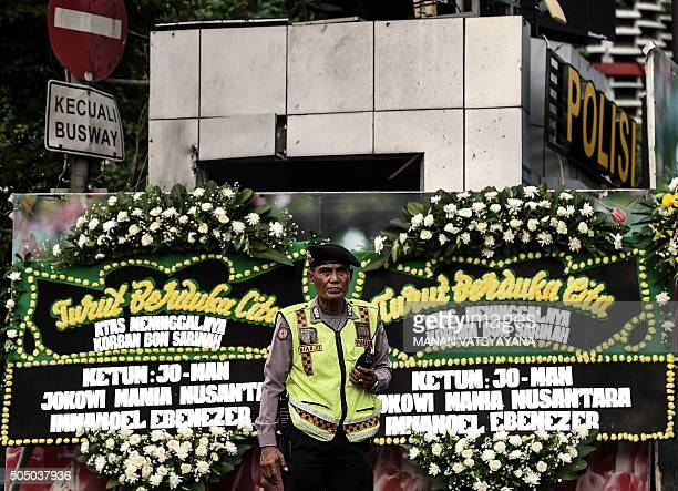 TOPSHOT An Indonesian traffic policeman stands in front of floral tributes set up at the blast site of the police outpost and opposite Starbucks in...
