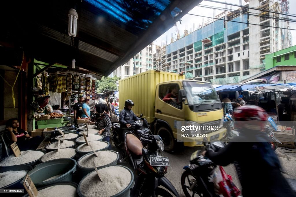 An Indonesian vendor (L) offers rice for sale along a busy lane at a traditional market in downtown Jakarta on February 21, 2018. /