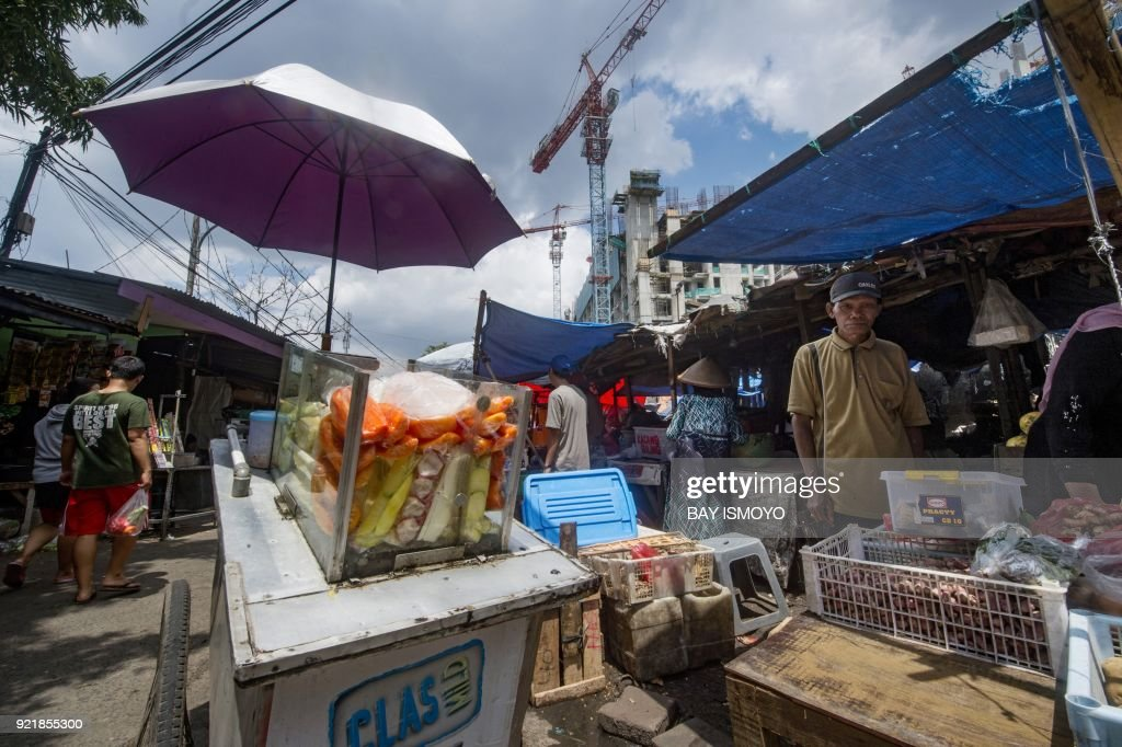 An Indonesian vendor (R) shelters in the shade at a traditional market in Jakarta on February 21, 2018. /