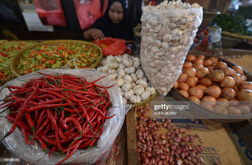 An Indonesian vendor (top C) waits for customers at a traditional market in Jakarta on April 1, 2013. Food ingredients quickened Indonesia's inflation in March to 5.9 percent year-on-year, surpassing the central bank's range target of 5.5 percent, the statistics office said on April 1. Indonesians who love adding lavish spices in their meal saw a steep rise in the prices of shallots, garlic and chili.