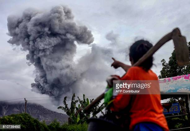 TOPSHOT An Indonesian villager gestures as Mount Sinabung volcano spews thick volcanic ash in Karo North Sumatra on July 8 2017 Sinabung roared back...