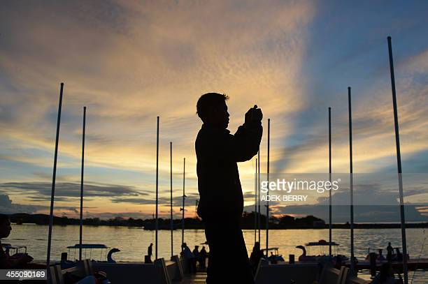 An Indonesian visitor takes photographs as the sun sets at Losari beach in Makasar, South Sulawesi on Desember 11, 2013. Indonesia's Ministry of...