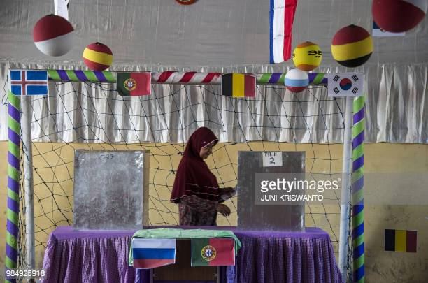 TOPSHOT An Indonesian voter casts her ballot at a footballthemed polling station decorated to attract voters with the ongoing Russia 2018 World Cup...