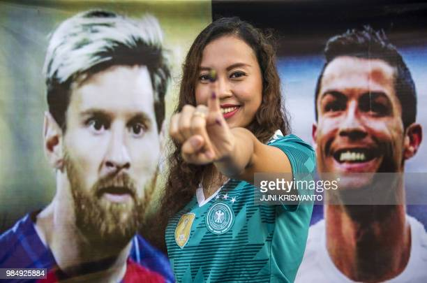 An Indonesian voter poses with her inked finger past portraits of football stars Lionel Messi and Cristiano Ronaldo at a footballthemed polling...