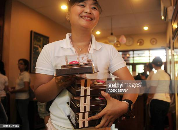 An Indonesian woman carries packs of Valentine's Day chocolates for sale at a shop in Jakarta on February 14 2012 Many Indonesian celebrated...
