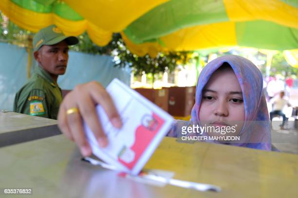 An Indonesian woman casts her vote in local elections at a polling station in Banda Aceh on February 15 2017 About 100 local elections are taking...