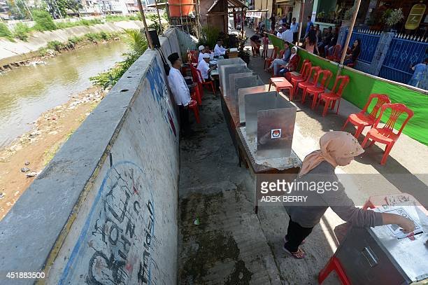 An Indonesian woman casts her vote in the country's presidential election at a makeshift polling centre in Jakarta on July 9 2014 Indonesians voted...