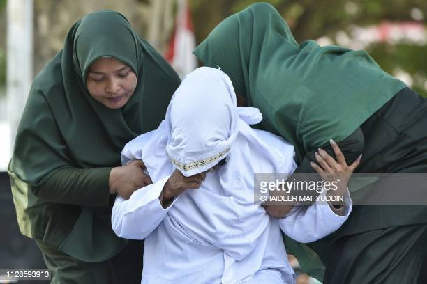 An Indonesian woman gets taken away after she was whipped in public in Banda Aceh on March 4 2019 Six couples were publicly whipped in Indonesia's...