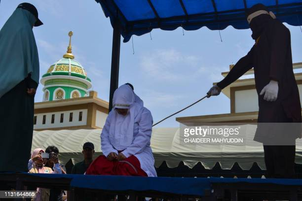An Indonesian woman is whipped by a member of the Sharia police in public in Banda Aceh on March 20 2019 A group of unmarried couples were whipped in...