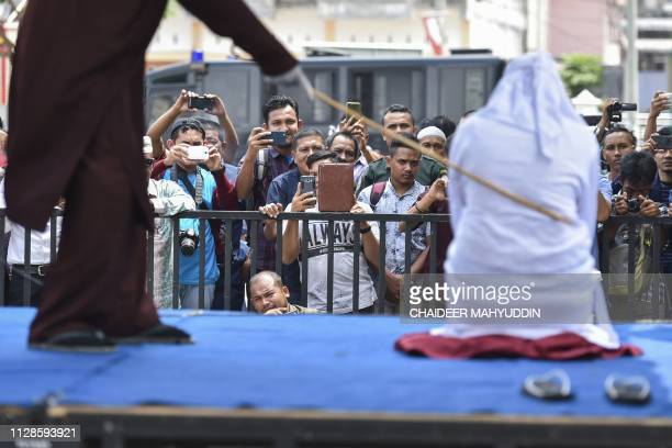 TOPSHOT An Indonesian woman is whipped in public in Banda Aceh on March 4 2019 Six couples were publicly whipped in Indonesia's conservative Aceh...