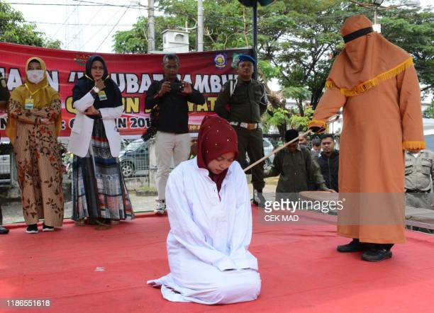 TOPSHOT An Indonesian woman is whipped in public on charges of engaging in sexual relations in Aceh Timur on December 5 2019 Two Indonesian men and a...