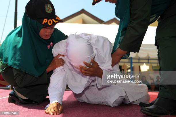 TOPSHOT An Indonesian woman known as Linda is helped by two Sharia officials after being caned for spending time in close proximity with a man who is...