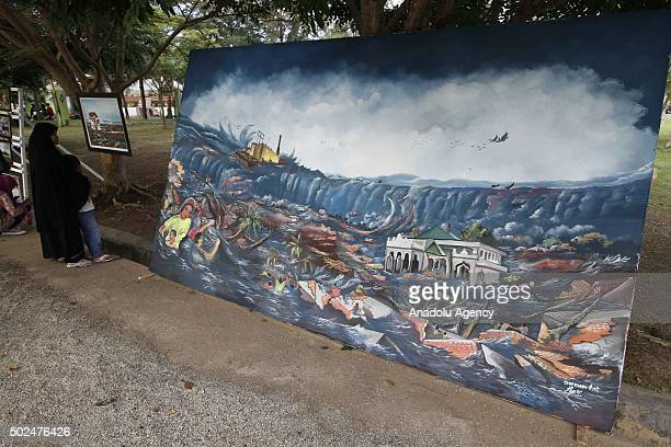 An Indonesian woman looks at a painting depicting the disaster as she visits the Ulee Lheue mass grave during the 11th anniversary of the 2004 Indian...