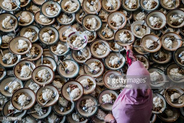 TOPSHOT An Indonesian woman prepares meals for Muslims breaking their fast during the holy month of Ramadan at Jogokariyan Mosque in Yogyakarta on...