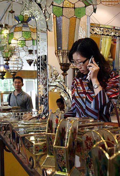 An Indonesian Woman L Talks On A Telep