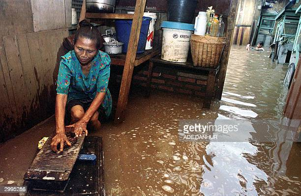 An Indonesian woman washes up while being surrounded by flood waters at their home in Jakarta 19 February 2004 Hundreds of people in Jakarta left...