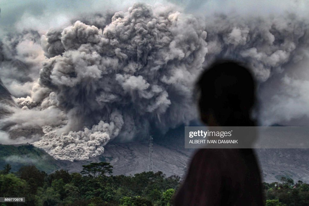 An Indonesian woman watches an eruption from the Mount Sinabung volcano from Tiga Pancur village, in Karo in North Sumatra on November 3, 2017. Sinabung roared back to life in 2010 for the first time in 400 years. After another period of inactivity it erupted once more in 2013, and has remained highly active since. /