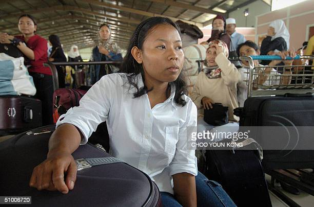 An Indonesian woman who has returned from Malaysia waits with others who have also returned from overseas some forcibly to have their papers...