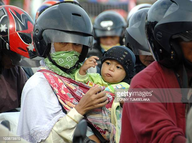 An Indonesian woman with her baby sit on a motorcycle as they wait to board a ferry headed for Java island in Gilimanuk port in on September 7 2010...