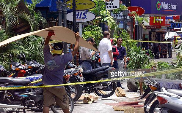 An Indonesian worker carries wood materials as foreign experts visit the blast site in Kuta 06 October 2005 where 19 people died from suicide bombers...