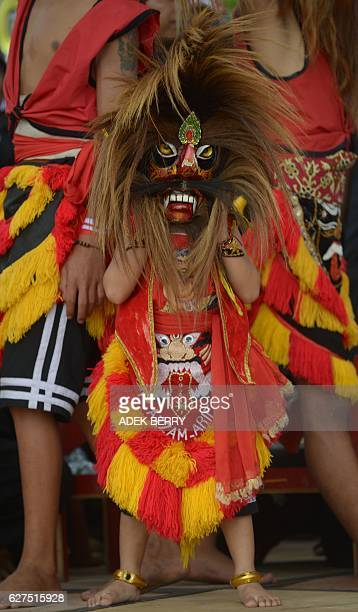An Indonesian young dancer performs the Reog Ponorogo traditional dancing as people attend a progovernment rally to call for unity in Jakarta on...