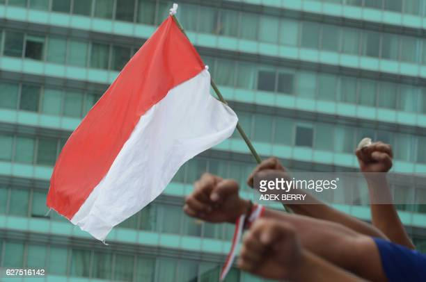 An Indonesia's flag and fists of Indonesian people who attend a progovernment rally to call for unity in Jakarta on December 4 2016 Thousands of...