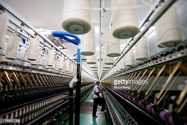 An Indorama Ventures Pcl employee works on a line of wool spinning machines at the Indorama Ventures Pcl factory in Kao Samoakoan Lopburi province...